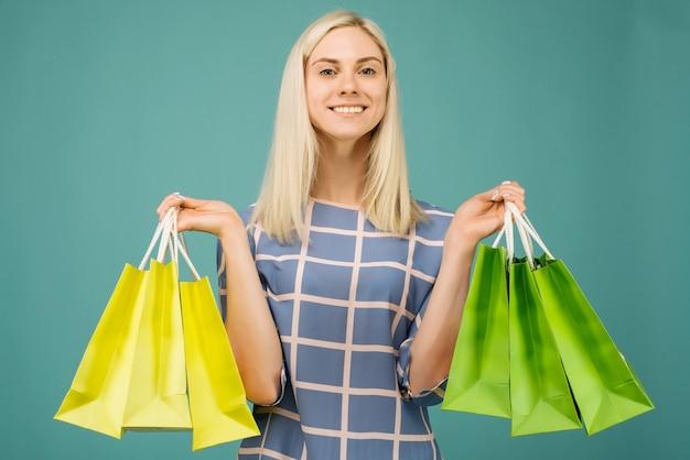 체크 무늬 블라우스에 행복 한 여자는 파란색에 쇼핑백을 보유