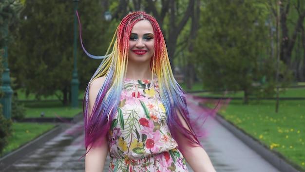Счастливая девушка в платье с радужными африканскими косичками и ярким красочным макияжем. мило улыбается, распускает волосы и кружится на прогулке в весеннем парке
