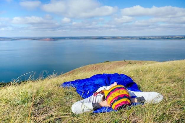 네팔에서 온 재미있는 모자를 쓰고 파란 침낭에 누워 호수 풍경을 바라보는 행복한 소녀