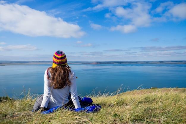 네팔에서 온 재미있는 모자를 쓰고 파란 침낭에 앉아 호수 풍경을 바라보는 행복한 소녀