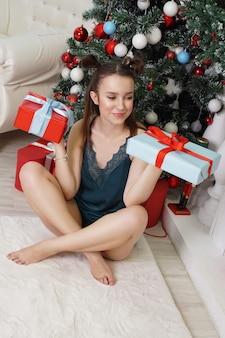 Счастливая девушка в зеленом пеньюаре и забавной прическе держит две подарочные коробки, не зная, какой подарок выбрать, чтобы подарить комнату, украшенную елкой
