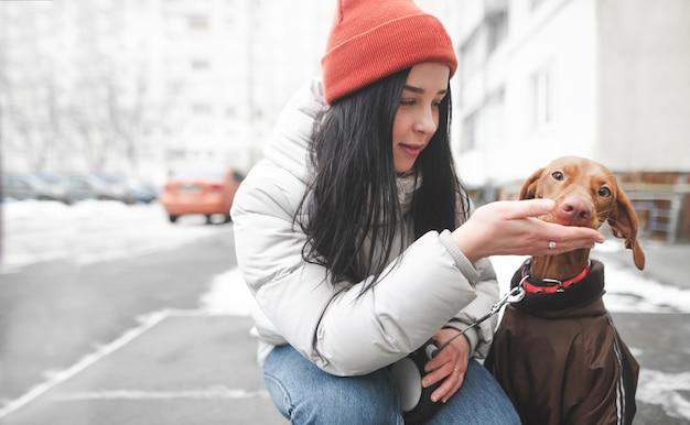 帽子と通りに座っていると彼女の犬に餌をやる冬の服で幸せな女の子