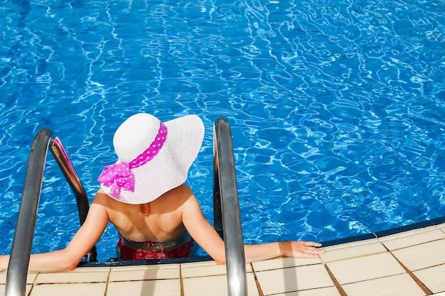 海のプールのそばで帽子をかぶった幸せな女の子