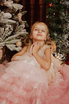 クリスマス ツリーの近くのピンクのドレスで幸せな女の子