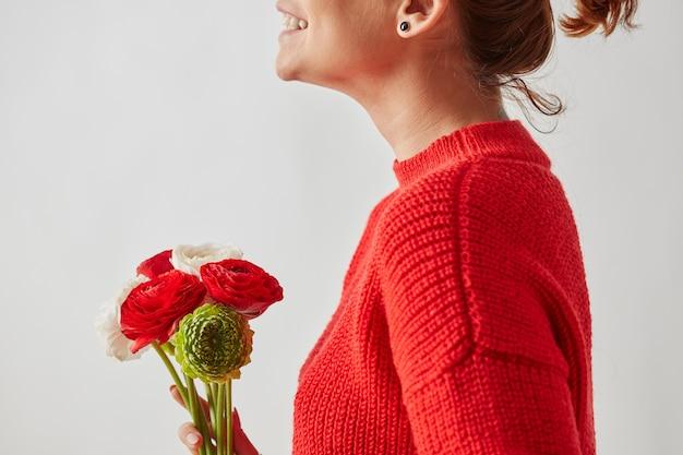 복사 공간이 있는 회색 배경 주위에 밝은 색의 라넌큘러스 꽃의 아름다운 꽃다발과 함께 빨간 니트 스웨터를 입은 행복한 소녀.