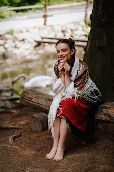 Счастливая девушка в украинском вышитом платье сидит на скамейке