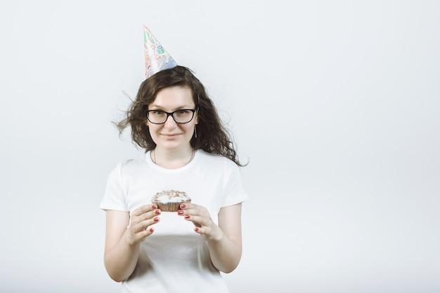 회색에 그녀의 손에 케이크와 함께 파티 모자에 흰색 티셔츠에 행복 소녀