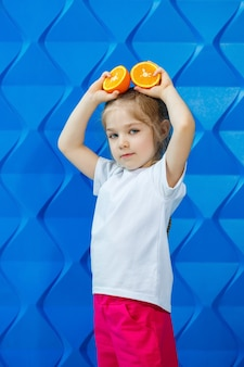 オレンジの半分を保持している髪を下に白いtシャツの幸せな女の子