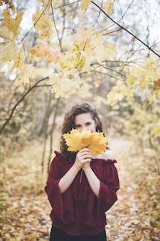 カエデの葉を保持しているアタムパークで幸せな女の子 Premium写真