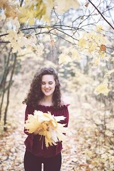 カエデの葉を保持しているアタムパークで幸せな女の子