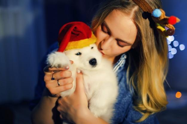クリスマスの装飾でサモエドハスキー犬と枝角の幸せな女の子