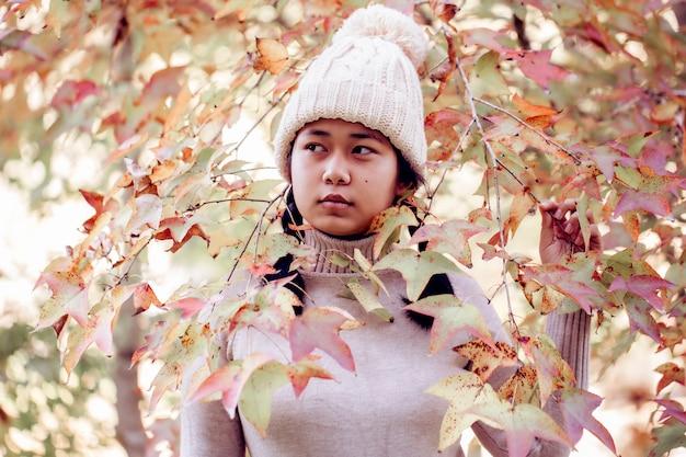 枝の間で秋の公園で幸せな女の子