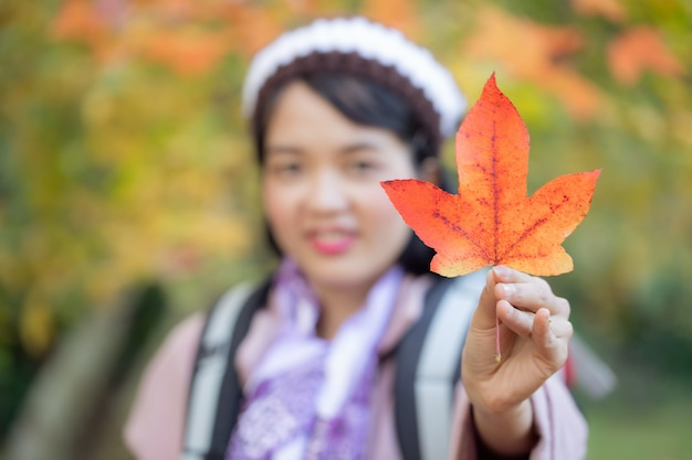 オレンジの葉を保持している秋の公園で幸せな女の子