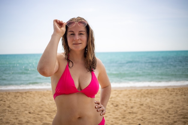 해변에서 비키니와 선글라스에 행복 한 소녀.