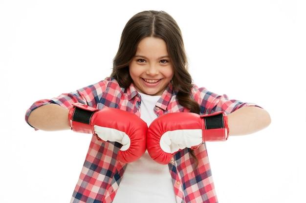 Счастливая девушка в боксерских перчатках, изолированных на белом. улыбка маленького ребенка в позе бокса. малыш-боксер готов к бою. спортивные тренировки и тренировки. готовы побеждать.