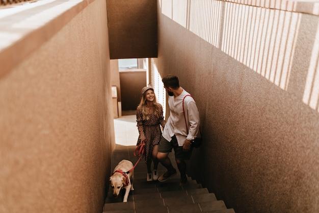 모자와 갈색 드레스를 입은 행복한 소녀와 그녀의 남자 친구가 개를 산책 할 계획을 세우고 웃고 계단을 올라갑니다.