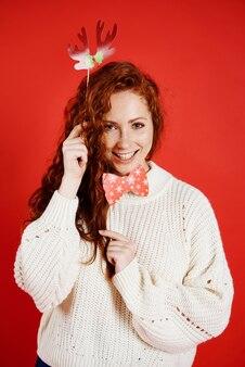 Счастливая девушка в рождественской маске на красной стене