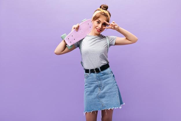 데님 스커트에 행복 한 소녀는 평화 서명을 보여주고 스케이트 보드를 보유하고 있습니다. 멋진 옷 포즈에 노란색 두건 유행 여자.