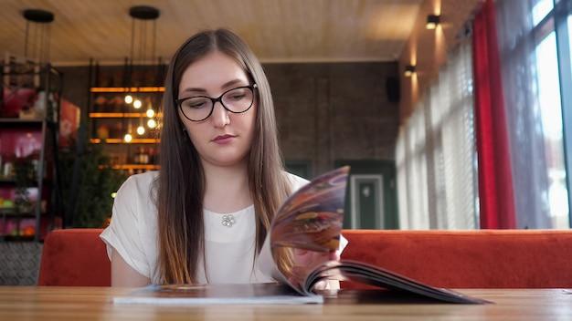 Счастливая девушка в очках в кафе, едят, глядя на меню ресторана.