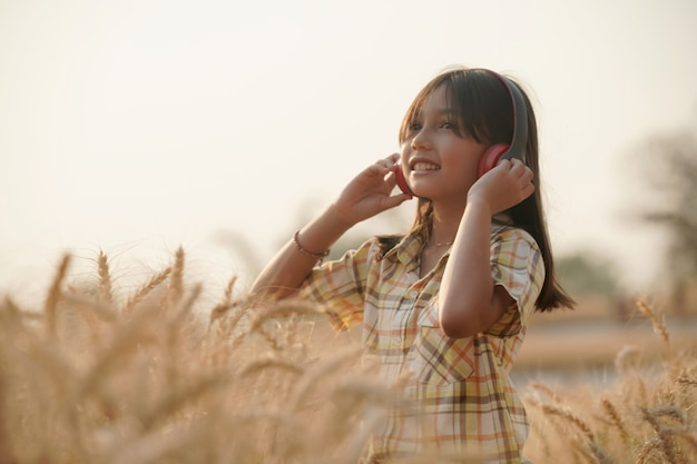 夏休みの黄金の麦畑夕焼けの幸せな女の子