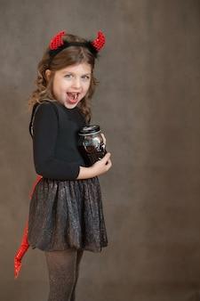 Счастливая девушка в чертовом костюме хэллоуина и стаканом крови