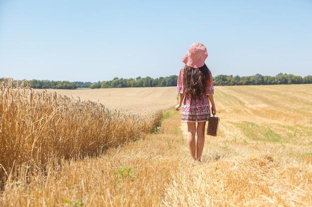 麦畑の帽子で幸せな女の子。大きな帽子と長い髪を吹く