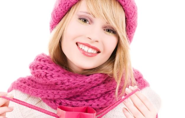Счастливая девушка в шляпе с розовой сумкой для покупок