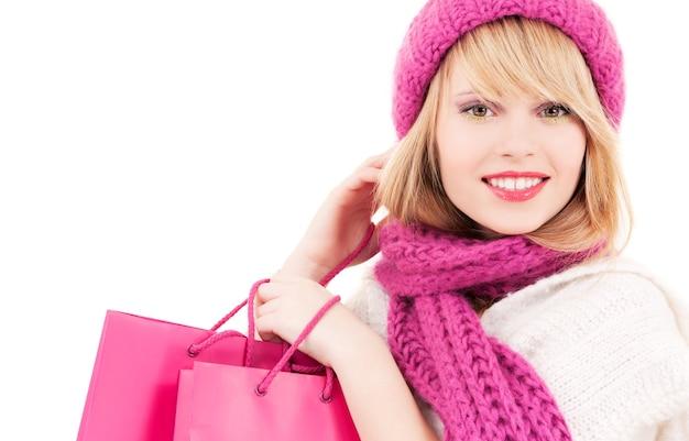 Счастливая девушка в шляпе с розовыми сумками