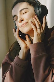 Счастливая девушка в наушниках слушает музыку дома