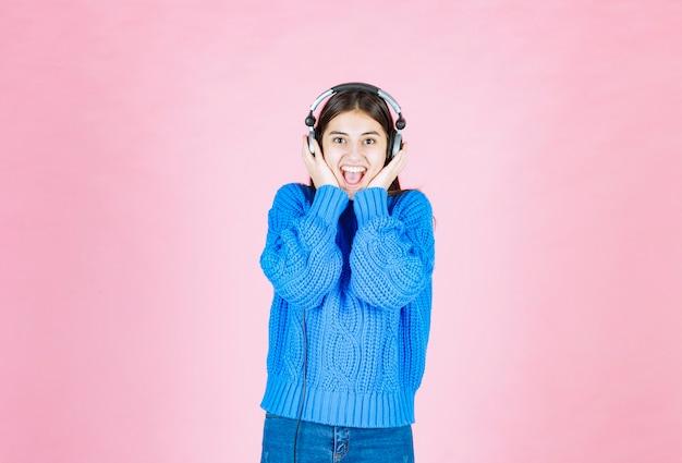 ピンクの上に立っているヘッドフォンで幸せな女の子。