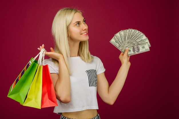 Счастливая девушка держит сто долларовые купюры и хозяйственные сумки на рубине