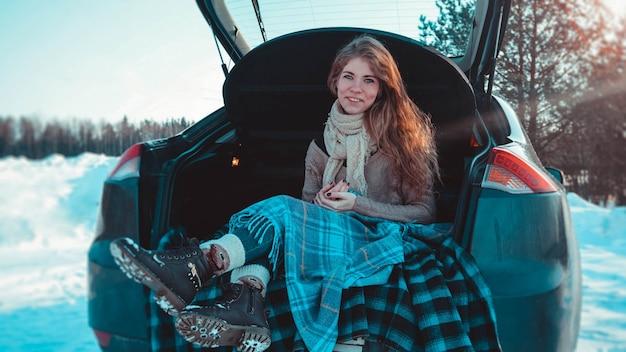 겨울 숲의 트럭에 앉아 니트 옷, 스카프, 격자 무늬를 입은 행복한 소녀 - 차로 여행