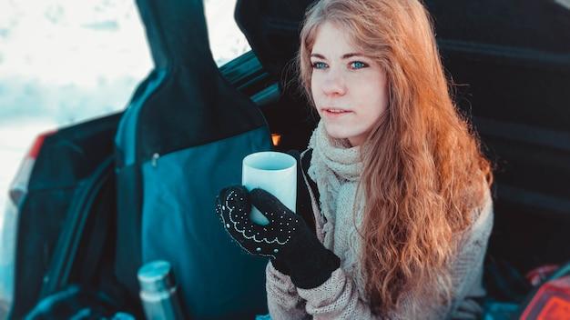 뜨개질을 한 옷, 스카프, 격자무늬 옷을 입은 행복한 소녀가 따뜻한 차나 커피 한 잔, 배경에 기타와 함께 겨울 숲의 자동차 트럭에 앉아 있습니다 - 차로 여행