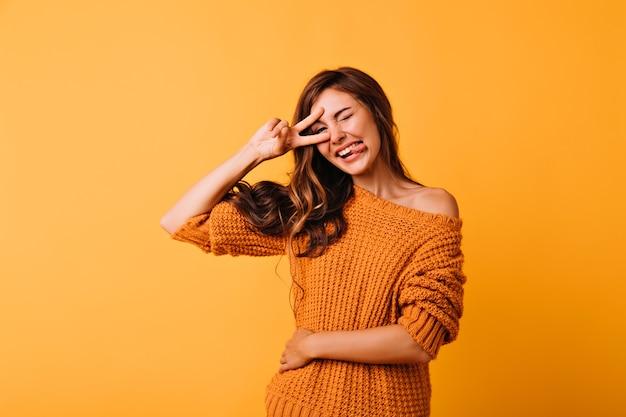 舌を出してポーズをとるニットセーターの幸せな女の子。変な顔をしているユーモアのある黒髪の女性のスタジオポートレート。