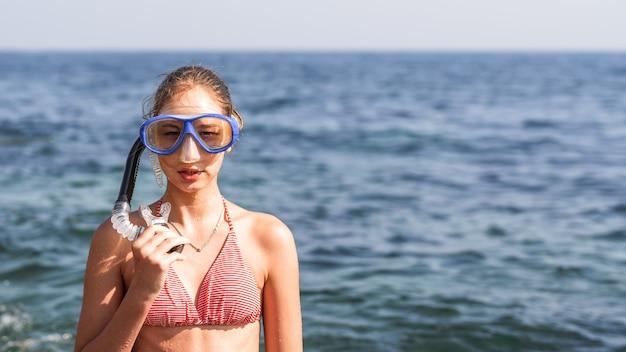 Счастливая девушка в маске и трубке на пляже