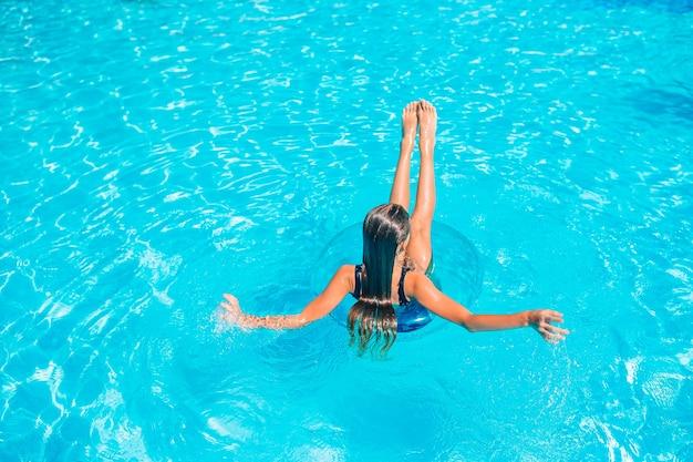 Счастливая девушка в открытом бассейне плавать и отдыхать
