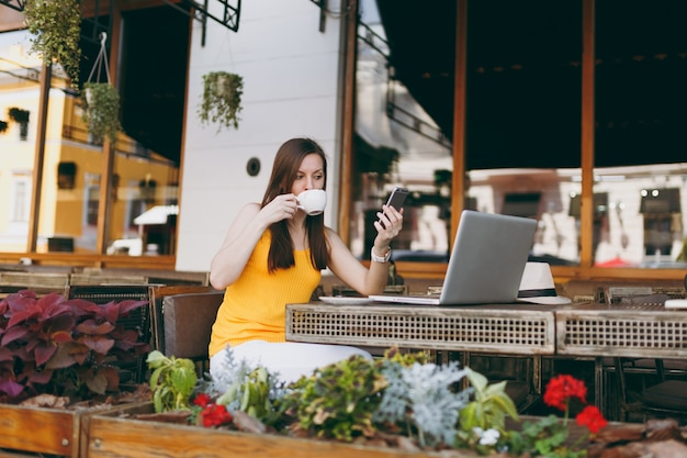 ラップトップpcコンピューター、携帯電話でのテキストメッセージメッセージ、自由時間中にレストランでカップティーを飲むとテーブルに座って屋外ストリートコーヒーショップカフェで幸せな女の子 Premium写真