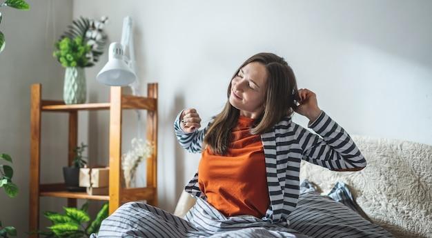 パジャマ姿の幸せな女の子が日当たりの良い寝室のベッドに座って、目を覚ますとストレッチ