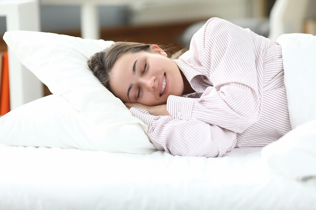 Счастливая девушка в пижаме лежит в постели, закрывая глаза