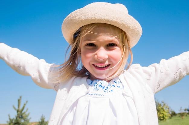 Счастливая девушка в панаме в солнечный летний день