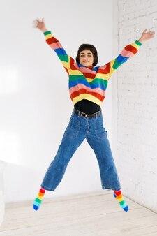 虹のセーターの幸せな女の子は、ハッピンでジャンプする明るい背景の白人の若い女性にジャンプします...
