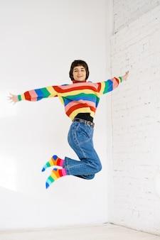 虹のセーターの幸せな女の子は、ハッピンでジャンプする明るい背景の白人の若い女性にジャンプします... Premium写真