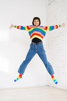 レインボーセーターの幸せな女の子が明るい壁にジャンプします