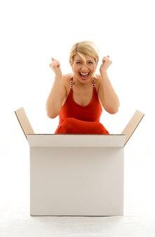 Счастливая девушка в красном платье с большой пустой белой коробкой