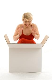 Счастливая девушка в красном платье с большой белой коробкой