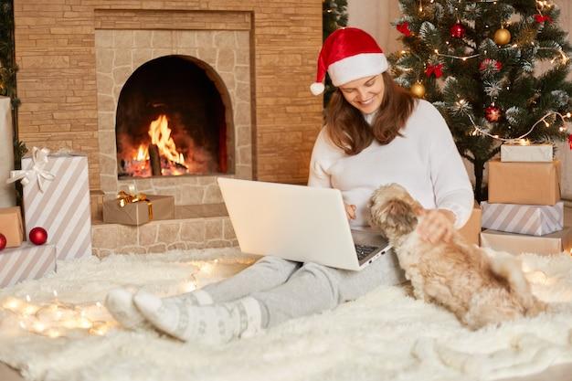 행복 한 표정으로 그녀의 북경 강아지를 찾고 여성 노트북과 함께 앉아 크리스마스 트리 조명, 벽난로 및 선물 축제 방에 귀여운 강아지와 함께 앉아 빨간 모자에 행복 한 소녀.