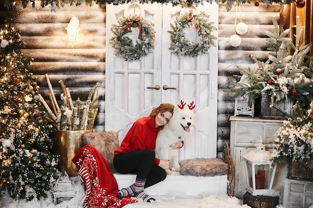 赤い新年のセーターとスカンジナビアの靴下で幸せな女の子が階段に座って、クリスマスのインテリアでかわいい白雪姫のサモエド犬とポーズをとっています。新年会と装飾の概念