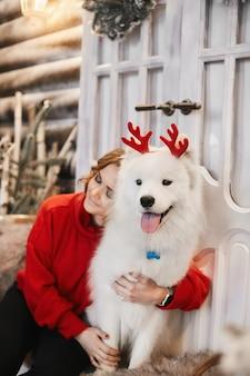 赤い新年のセーターを着た幸せな女の子が階段に座って、小さな赤い鹿の角でかわいい白いサモエド犬を抱き締めます。クリスマスの装飾の概念。新年会。