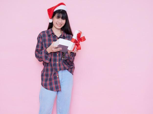 ピンクの壁にギフトボックスを開くサンタ帽子の幸せな女の子