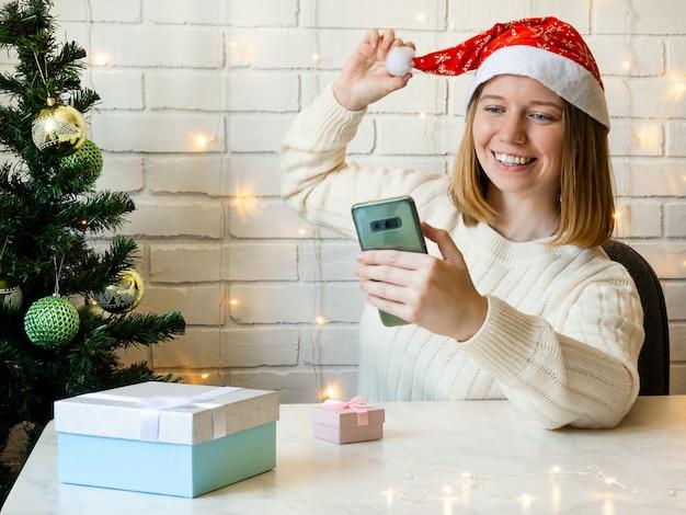 サンタさんの赤い帽子をかぶった幸せな女の子が電話で友達とチャットします。コンセプトオンラインクリスマス